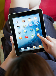 Woman using an iPad tablet computer at home