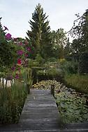 2.000 qm Grundstück, vier Teiche, am großen Teich mit Wasserlauf zwei Holzterrassen. Kleiner Beach mit Sonneninsel. Viele Sitzgelegenheiten umrahmt von Stauden, Sommerblumen, Wildblumenwiese und kleinem Gemüsegarten.