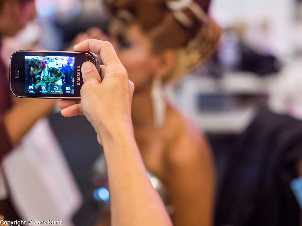 24 JULY 2013 - BANGKOK, THAILAND:  A woman uses her cell phone to make pictures of a model having her hair and makeup done at the Hairworld Festival in Siam Paragon, an upscale shopping mall in Bangkok, Thailand.        PHOTO BY JACK KURTZ