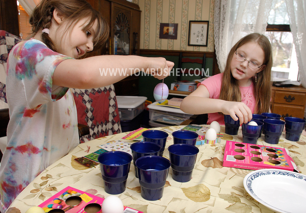 Middletown, N.Y. - A 7-year-old girl, left, and her 9-year-old sister color Easter eggs on April 15, 2006. MR