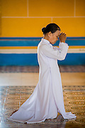 """29 MARCH 2012 - TAY NINH, VIETNAM:  A Cao Dai adherent prays in the main hall of the Cao Dai Holy See in Tay Ninh, Vietnam. Cao Dai (also Caodaiism) is a syncretistic, monotheistic religion, officially established in the city of Tây Ninh, southern Vietnam in 1926. Cao means """"high"""" and """"Dai"""" means """"dais"""" (as in a platform or altar raised above the surrounding level to give prominence to the person on it). Estimates of Cao Dai adherents in Vietnam vary, but most sources give two to three million, but there may be up to six million. An additional 30,000 Vietnamese exiles, in the United States, Europe, and Australia are Cao Dai followers. During the Vietnam's wars from 1945-1975, members of Cao Dai were active in political and military struggles, both against French colonial forces and Prime Minister Ngo Dinh Diem of South Vietnam. Their opposition to the communist forces until 1975 was a factor in their repression after the fall of Saigon in 1975, when the incoming communist government proscribed the practice of Cao Dai. In 1997, the Cao Dai was granted legal recognition. Cao Dai's pantheon of saints includes such diverse figures as the Buddha, Confucius, Jesus Christ, Muhammad, Pericles, Julius Caesar, Joan of Arc, Victor Hugo, and the Chinese revolutionary leader Sun Yat-sen. These are honored at Cao Dai temples, along with ancestors.    PHOTO BY JACK KURTZ"""