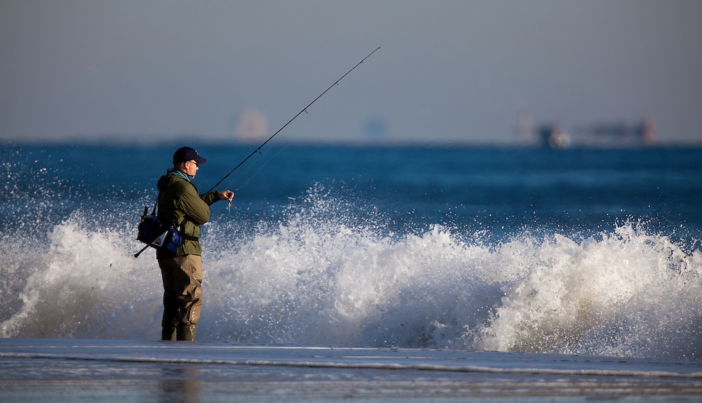 A fisherman working the shoreline at Sandy Hook NJ during high surf conditions on a falling tide.   The fall fishing run of striped bass and bluefish is legendary at the park.