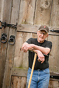 Bob Denman with one of his tools in front of the forge at Red Pig Garden Tools