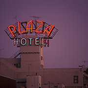 Lit neon signage reading Plaza Hotel on top of a building in San Diego, CA