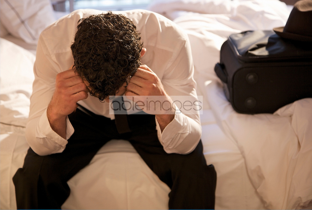Businessman sitting on a bed with his head in his hands