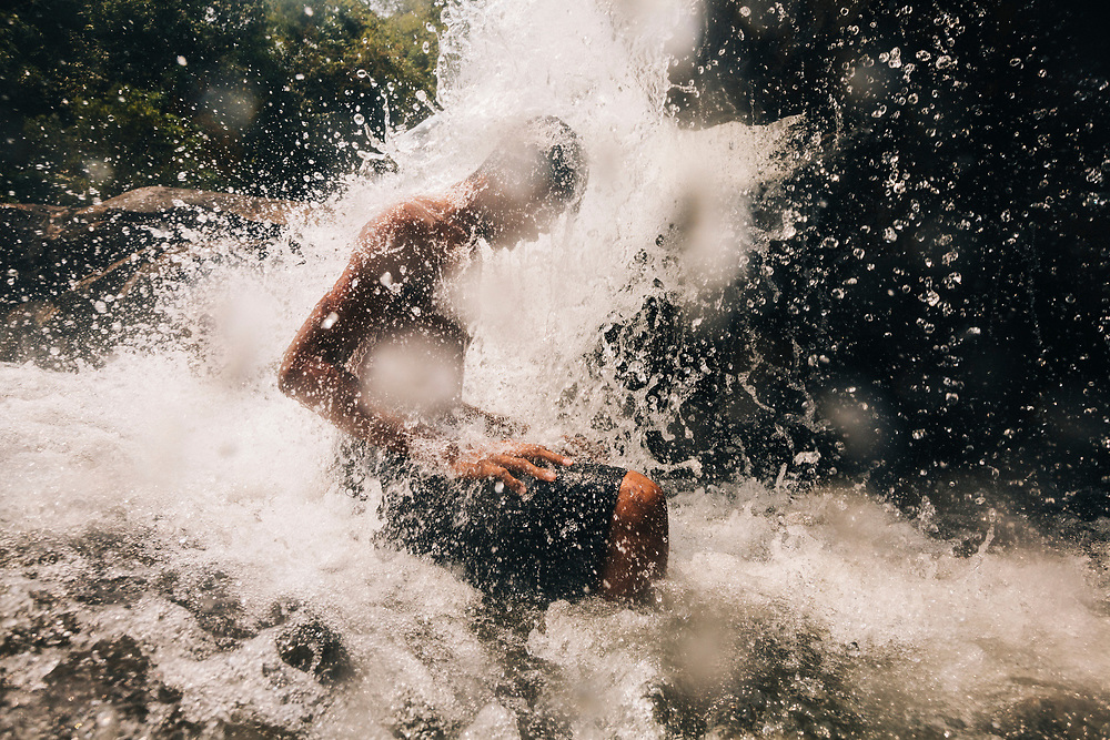 A young man gets splashed by a waterfall in Koh Kong, Cambodia.