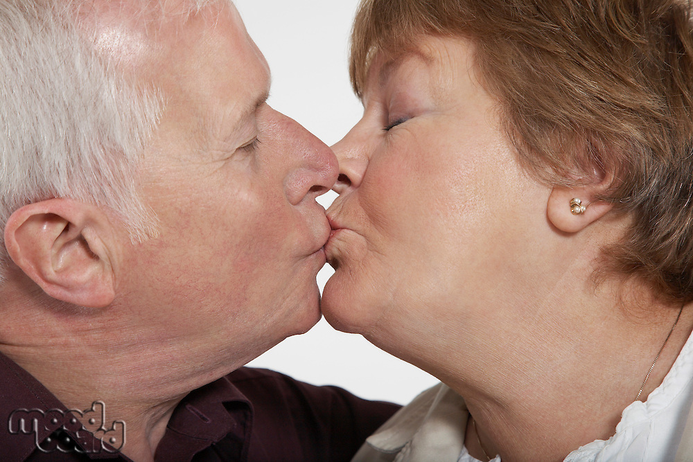 Profile of middle-aged couple kissing close-up