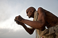A pilgrim makes an offering to the Ganges River on an early October morning in Varanasi, India.