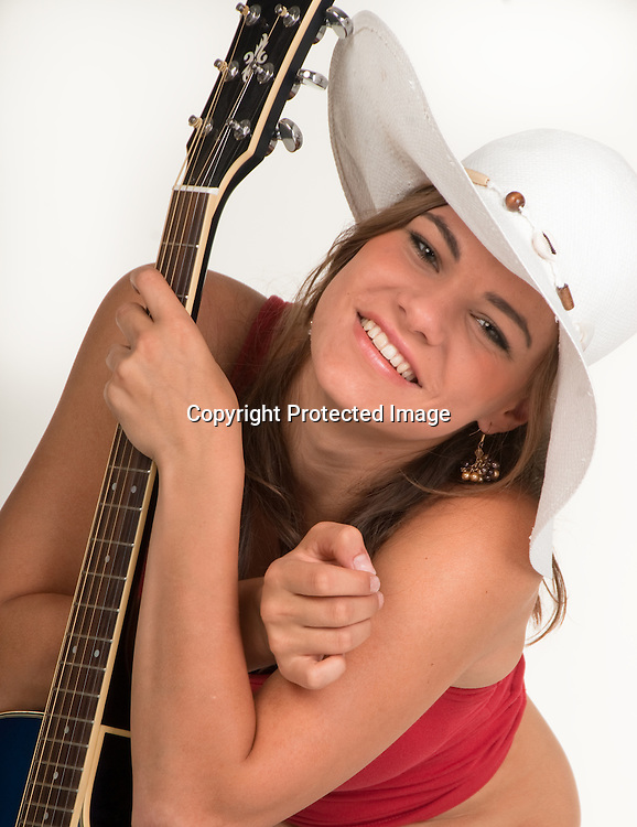 a young girl smiling, holding a guitar