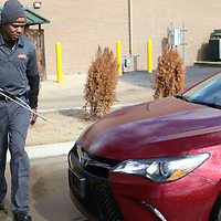 Bernard McMillion sprays Bug Whacker Juice onto a vehicle Saturday before proceeding through the carwash