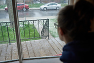 Alexandria MacLellan looks through the front window of her home during a hail storm during the COVID-19 pandemic in April 2020 in Windsor, Ontario.