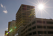 Idaho. Downtown Boise. Sunburst behind downtown buildings.