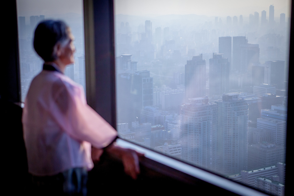 """Woman in traditional Korean clothes watching the Seoul skyline at """"The 63 Building"""", officially the 63 City, at a skyscraper on Yeouido island, overlooking the Han River in Seoul, South Korea."""