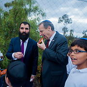 Mayor Bob Filner enjoys a jelly donut offered to him by a student at Chabad Hebrew Academy after he lit a menorah at their school.