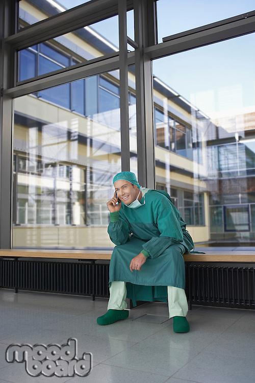 Surgeon sitting in hospital corridor using mobile phone