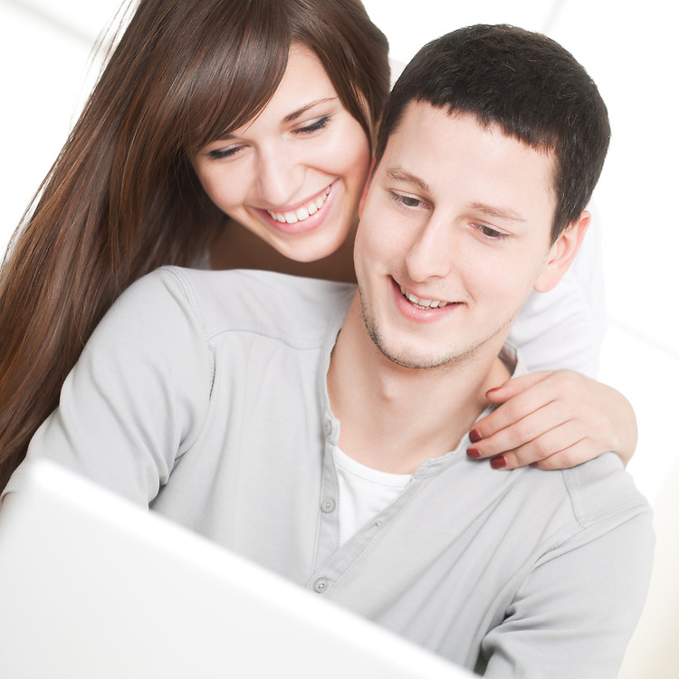Portrait of a happy couple using laptop in the living room.