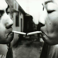 "BEIJING, HAIDIAN DISTRICT, CHINA - AUGUST 12: Shen Yue (L) and Tu Qiang (R) share a cigarette in the afternoon in the alley where the Scream Bar is located August 12, 1998 in the Haidan district of Beijing, China. The Beijing punks spend their afternoons smoking and drinking in the alley before they get ready to perform at the Scream Bar. In the spring of 1998, a handful of youngsters teamed up to unofficially rebel against conformist Chinese life. They shaved their heads, and founded bands with names like ""Brain Failure"" and ""Anarchy Boys."" Although the majority of the punks came from well-off families, they preferred to live in self-imposed poverty. The Scream Bar and its surrounding dusty alleyways in the student district became the center of youthful rebellion until it was finally closed in 2000. The punks bands have moved on to other bars in Beijing, some received contracts with foreign record companies and even toured in Europe, Japan and the U.S."