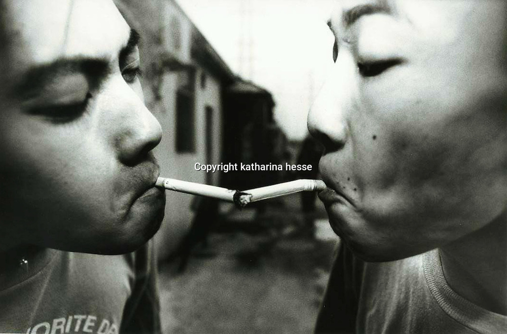 """BEIJING, HAIDIAN DISTRICT, CHINA - AUGUST 12: Shen Yue (L) and Tu Qiang (R) share a cigarette in the afternoon in the alley where the Scream Bar is located August 12, 1998 in the Haidan district of Beijing, China. The Beijing punks spend their afternoons smoking and drinking in the alley before they get ready to perform at the Scream Bar. In the spring of 1998, a handful of youngsters teamed up to unofficially rebel against conformist Chinese life. They shaved their heads, and founded bands with names like """"Brain Failure"""" and """"Anarchy Boys."""" Although the majority of the punks came from well-off families, they preferred to live in self-imposed poverty. The Scream Bar and its surrounding dusty alleyways in the student district became the center of youthful rebellion until it was finally closed in 2000. The punks bands have moved on to other bars in Beijing, some received contracts with foreign record companies and even toured in Europe, Japan and the U.S."""