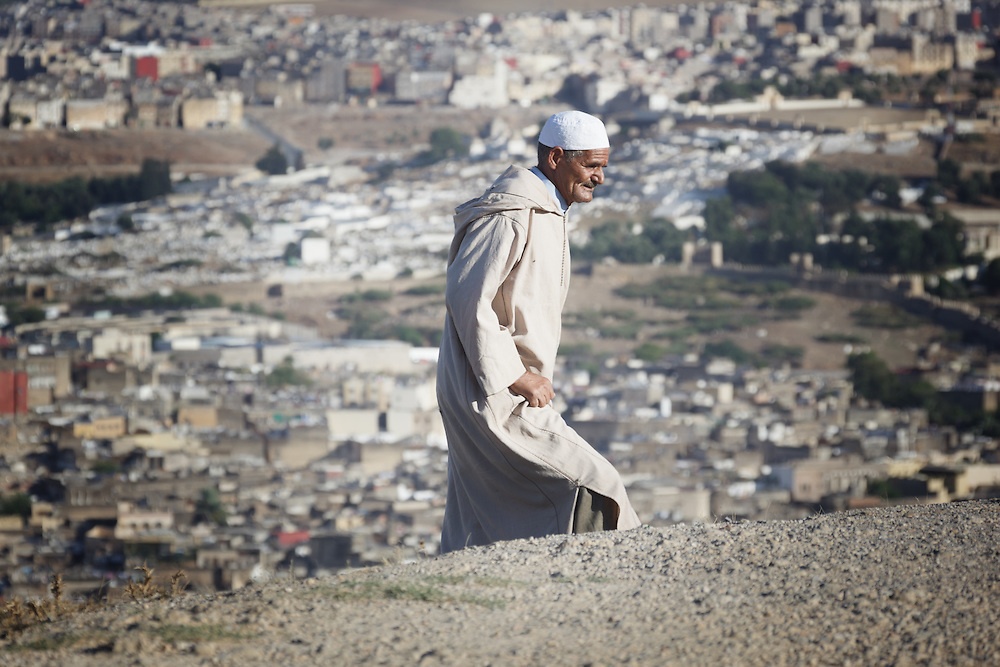 A traditional dressed old man walks on a hill against the old city of Fès.