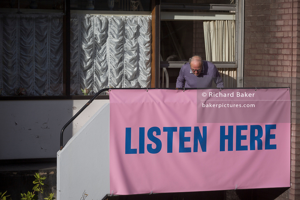 "A resident of Bowater House on the Golden Lane Estate cleans a window with a banner on the balcony protesting about the 10-storey luxury apartment development called The Denizen, a controversial building by Taylor Wimpey that locals say will dominate their view and block their daylight, on 30th October 2017, in London, England. Residents on the Estate have erected banners by artists Jeremy Deller and Elizabeth Price to picket the developers. Despite this, Wimpey say, ""We are one of the UK's largest residential developers. As a responsible developer we are committed to working with local people and communities."""