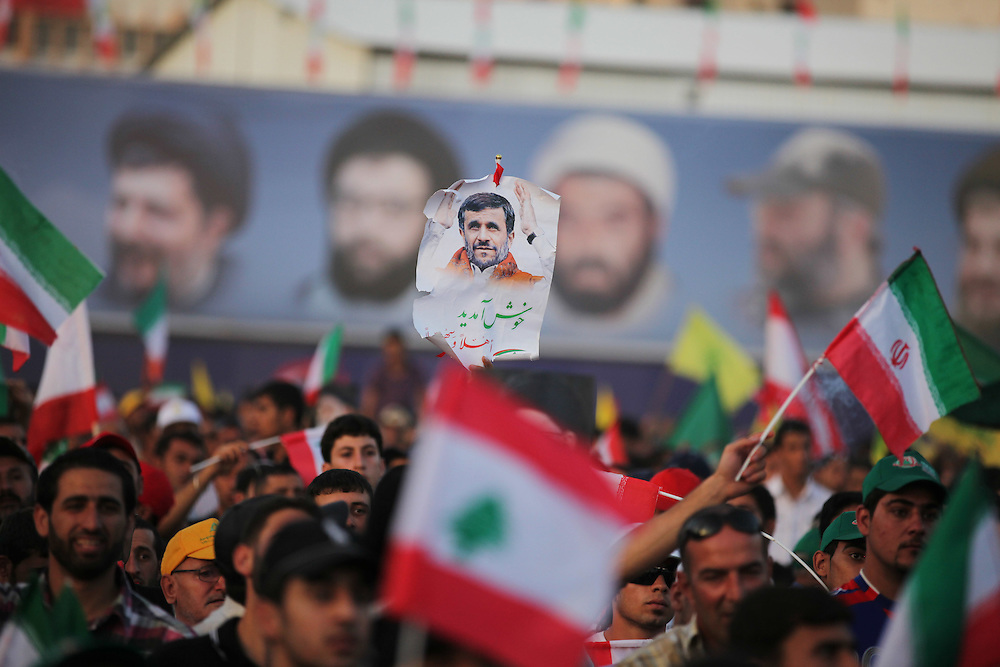 On the second and final day of his visit to Lebanon, Iranian President Mahmoud Ahmadinejad traveled to the southern town of Bint Jbeil. There a Hizballah-organized rally was held to welcome Ahmadinejad to the south Lebanon, an area where Hizballah is widely supported. Tens of thousands gathered for hours holding flags of Iran, Hizballah, Lebanon and other political parties, cheering the Iranian president as he arrived by helicopter from Beirut. ///People hold a picture of Iranian President Mahmoud Ahmadinejad at a stadium in Bint Jbeil while he addresses the crowd.