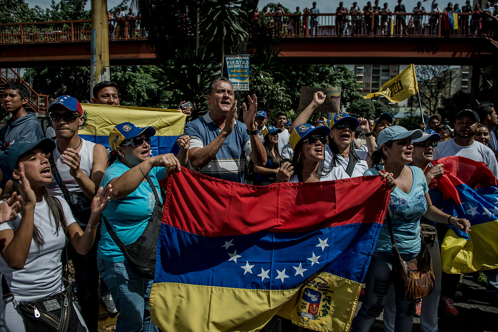 """CARACAS, VENEZUELA - APRIL 19, 2017:  Protesters in """"La Vega"""" slum in Caracas shout while holding the Venezuelan flag upside-down. This protest was significant, because it was the firt time that a significant people from the slums came down to join an opposition march, which usually consists of middle-class protesters.   Thousands of protesters took to the streets today in Venezuela to show their discontent with the government.  They were met by riot police that fired tear gas and rubber bullets at them.  Some protesters responded by throwing rocks and petrol bombs.  Venezuela is in crisis, and residents face daily struggles over food and medicine shortages, and one of the highest crime rates in the world.  PHOTO: Meridith Kohut"""