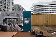 "An outdoor exhibition panel near the former Checkpoint Charlie, the former border between Communist East and West Berlin during the Cold War. The Berlin Wall was a barrier constructed by the German Democratic Republic (GDR, East Germany) starting on 13 August 1961, that completely cut off (by land) West Berlin from surrounding East Germany and from East Berlin. The Eastern Bloc claimed that the wall was erected to protect its population from fascist elements conspiring to prevent the ""will of the people"" in building a socialist state in East Germany. In practice, the Wall served to prevent the massive emigration and defection that marked Germany and the communist Eastern Bloc during the post-World War II period."