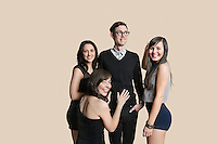 Portrait of beautiful women surrounding mid adult man over colored background