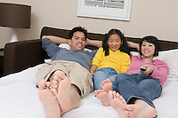 Mother, father and daughter lying down on bed and watching TV