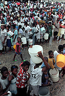 Thousands of people stand in line to fill containers with clean water in Port-au-Prince, Haiti, May 1995. (Photo by Roger M. Richards)