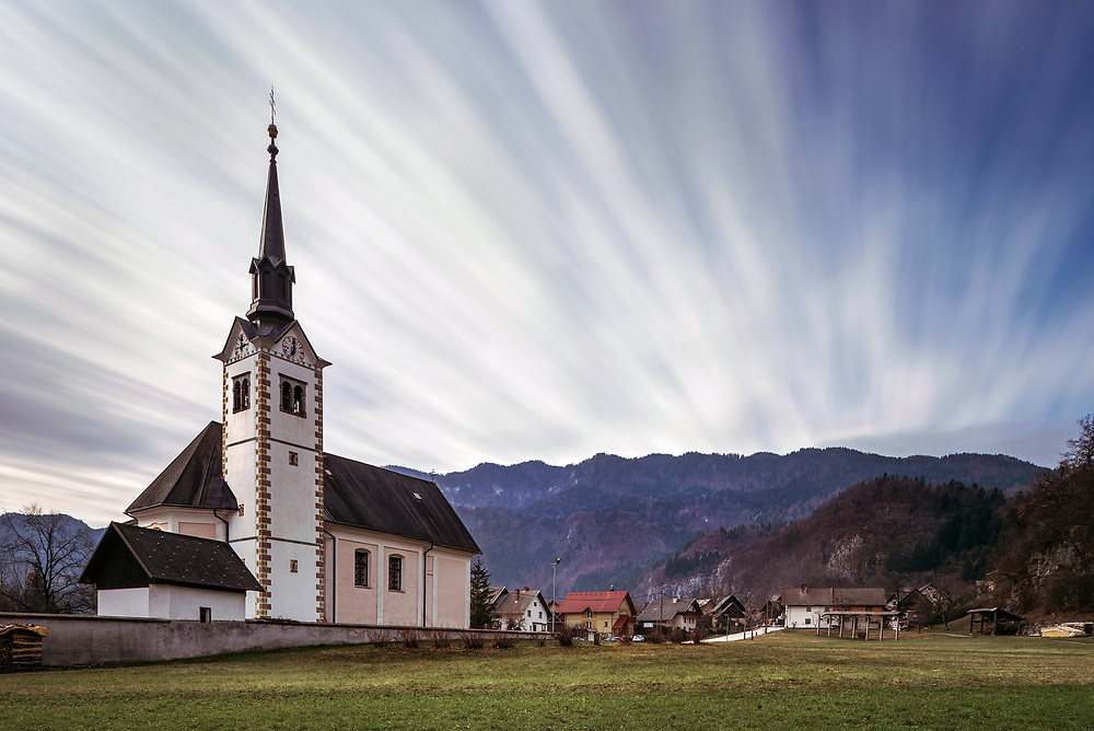 Long exposure architecture/landscape image of church on winter's day near Lake Bled, Slovenia, looking over the Julian Alps