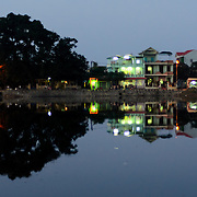 A neighborhood street is reflected on the glassy calm surface of the Perfume River at dusk in Hue, Vietnam.