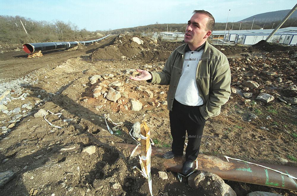 Buergermeister Vano Tsiklauri steht auf der von BTC Pipeline-Baumaschinen beschaedigten Haupttrinkwasserleitung seiner KLeinstadt Tetritskaro. Links die BTC Pipeline, recht ein Camp fuer Pipelinearbeiter. Tsiklauri aergert sich, dass der Pipeline Betreiber British Petrol den Schaden nicht regulieren...Vano Tsiklauri, Mayor of Tetritskaro at the BTC contruction Site to inspect a broken water supply.