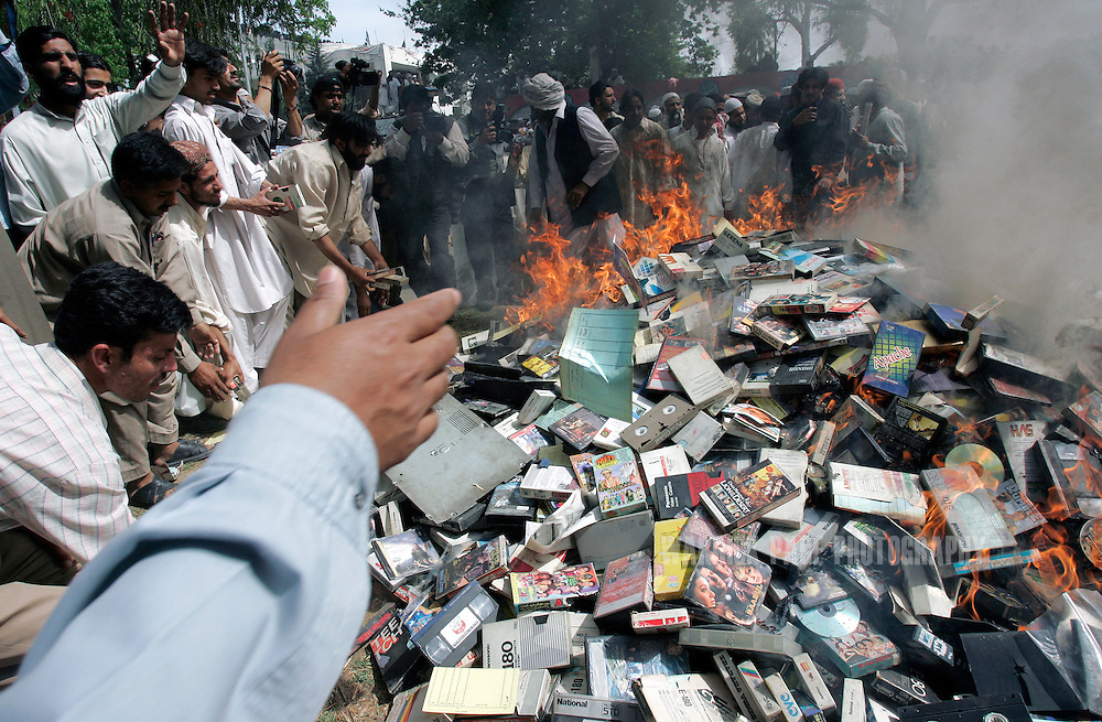ISLAMABAD, PAKISTAN - APRIL 6: Students of the hard-line Islamic madrassa, Lal Masjid (Red Mosque) burn CDs, DVDs, televisions and VCRs in a protest against vice in Islamabad, April 6, 2007, Islamabad, Pakistan. In a siege lasting a week beginning July 3, 2007, Pakistani special forces stormed the madrassa compound on July 10, killing an unknown number of militants and students, with reports varying from 200 to more than 1000 killed. The incident propelled Pakistan into greater turmoil with regular attacks from militant groups against government and military instillations, resulting in terrorist-related deaths numbering more than 800 in 2007. (Photo by Warrick Page)