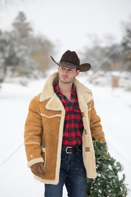 hot cowboy in Winter walking with a Christmas wreath