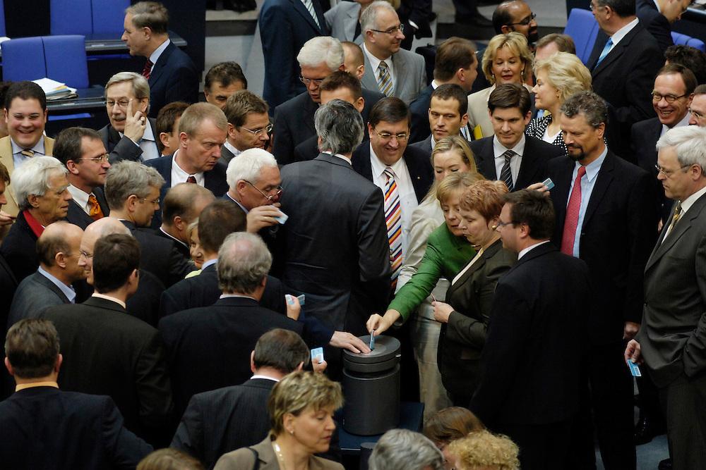 01 JUN 2006, BERLIN/GERMANY:<br /> Angela Merkel (halb verdeckt neben der Wahlurne), CDU, Bundeskanzlerin, wirft Ihre Stimmkarte ein, waehrend der namentlichen Abstmmung zum Einsatz der Bundeswehr im Kongo im Rahmen der EU-gefuehrten Operation EUFOR RD Congo, Plenum, Deutscher Bundestag<br /> IMAGE: 20060601-01-088<br /> KEYWORDS: Plenarsaal, Übersicht