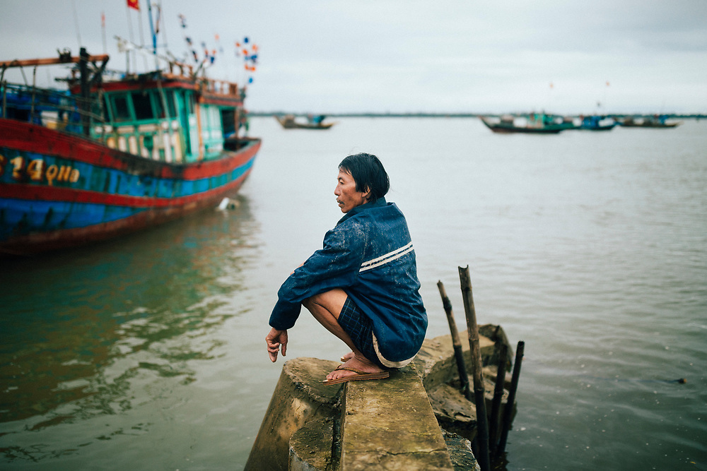 A Vietnamese man sits along the Thu Bon River in the early morning hours in Hoi An, Vietnam.