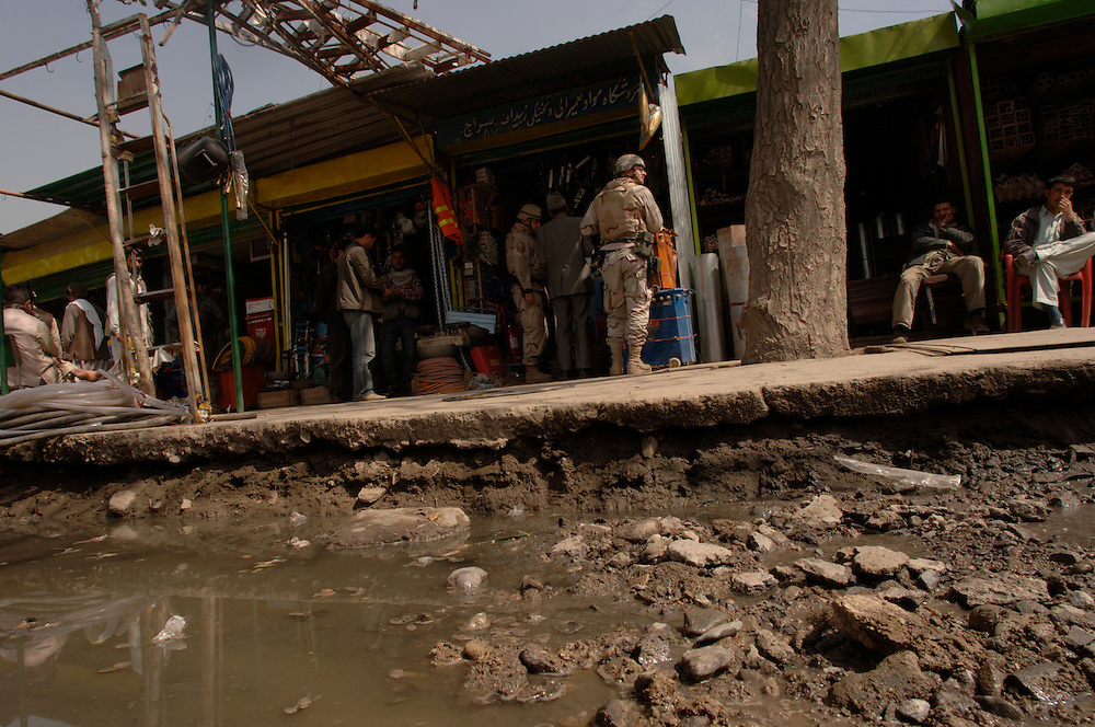 In the other side of a gutter, Major David Gehrich (center right), scans the sidewalk area while Mr. Mohammad Essaq (center), interpretes for Master Sgt. Martin Fox (center left) during a 4 April 2006 local purchase.  The material will support the U.S. Air Force and the Afghanistan National Army (ANA). The shops are converted containerized cargo containers set side by side. Major Gehrich, a native of Brooksville, Fl. is deployed to the 755th Expeditionary Mission Support Group, Detachment 2, Camp Eggers, Kabul, Afghanistan, and a member of an U.S. Air Force Embedded Training Team (EET). He is assigned to the Air Force Logistics Management Agency, Maxwell Air Force Base, Gunter Annex, Ala. ETTs are fulfilling an U.S. Army request for forces in support of Office of Security Cooperation-Afghanistan (OSC-A) mission to advise, train and mentor Afghanistan National Army personnel on the U.S. Army logistics standard and methods.  The purchase of needed supplies and personal protection equipment will allow the ETT to continue mentoring the ANA, and for the ANA to operate safely and prepare for future missions. At the Central Workshop, reconditioning of small arms such as AK-47 rifles to field artillery repairs are performed. The funds for the purchases come from Field Ordering Officer funds that are used if items are not available from the Office of Security Cooperation-Afghanistan (OSC-A) or ANA supply systems in the time required -- purchases can not exceed $2,500.  The U.S. Air Force provides specialized personnel to fill U.S. Army request for forces.  This supports the OSC-A in its partnership with the Government of Afghanistan and the International Community to plan, program, and implement reform in Defense Sectors, develop a stable Afghanistan, and deter and defeat terrorism within its borders. (U.S. Air Force photo/Master Sgt. Lance Cheung)<br />