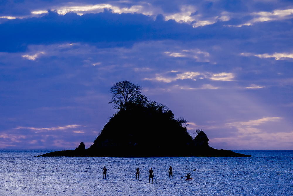 A group of paddle boarders and one sea kayaker head out towards an island off the coast of Playa Danta in Costa Rica.