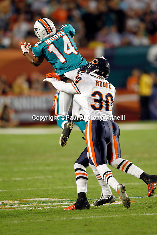 Miami Dolphins wide receiver Marlon Moore (14) leaps while trying to catch an incomplete third quarter pass while covered by Chicago Bears cornerback D.J. Moore (30) during the NFL week 11 football game against the Chicago Bears on Thursday, November 18, 2010 in Miami Gardens, Florida. The Bears won the game 16-0. (©Paul Anthony Spinelli)