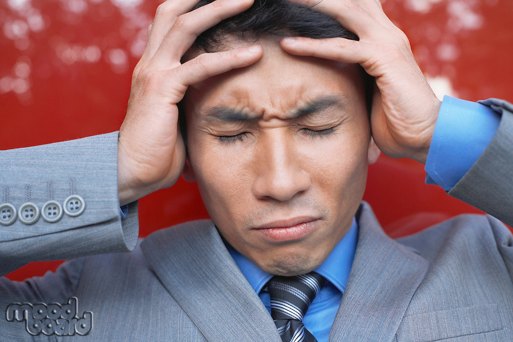 Stressed Businessman holding head in hands eyes closed close-up