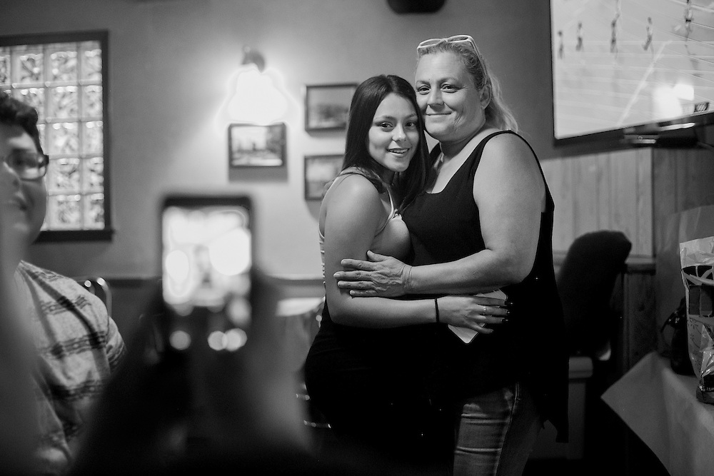 """CHICAGO, IL - AUGUST 14, 2016: Miranda Mercado embraces her mother Diana Mercado at a """"trunk party"""" just days before starting her freshman year of college. Mercado's sister, Veronica Lopez, 15, was shot and killed over Memorial Day weekend while riding in a car with friends. CREDIT: Sam Hodgson for The New York Times."""