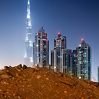United Arab Emirates, Dubai, Debris pile in front of Burj Khalifa and construction site of new office towers and apartment blocks in Business Bay district at night