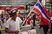 "May 12 - BANGKOK, THAILAND: A Thai Red Shirt carries the Thai flag through the crowd in front of the Red Shirts' main stage Wednesday. The Thai government said Wednesday that time has run out for ""Red Shirt"" protesters in Ratchaprasong and Sala Daeng intersections in Bangkok and that a crackdown could come at any time. As news of the anticipated crackdown spread, Red Shirt protesters continued with an almost festive mood at their main stage but many of the sleeping areas around the protest site appeared to be empty. No official estimates on crowd size are available.  Photo by Jack Kurtz"