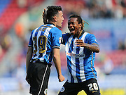 Tim Chow scores to make it 1-0 to Wigan Athletic and celebrates with Wigan Athletic defender Gaetan Bongduring the Sky Bet Championship match between Wigan Athletic and Brighton and Hove Albion at the DW Stadium, Wigan, England on 18 April 2015.