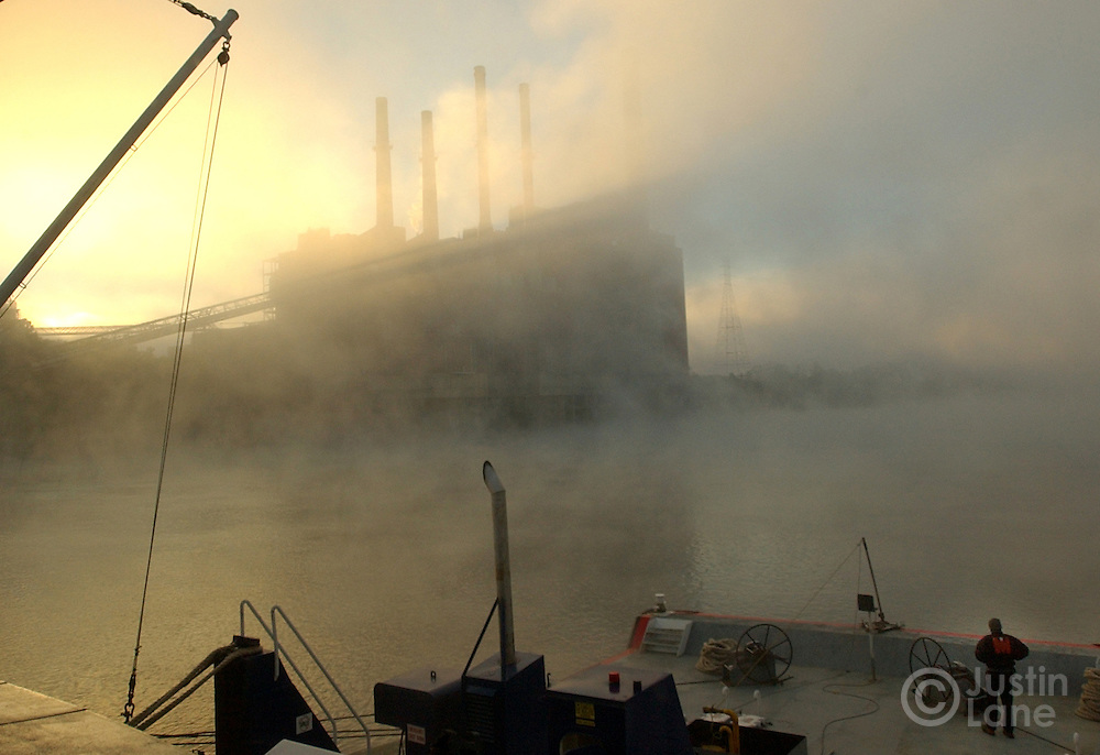 10/7/04--OHIO RIVER--.Early morning fog is seen along the Ohio River and around a factory on the riverside as a crew member of the River Explorer, right, keeps an eye where the barge is going..JUSTIN LANE FOR THE NEW YORK TIMES