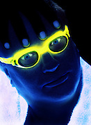 Portrait of a man with glowing goggles and towel.Black light