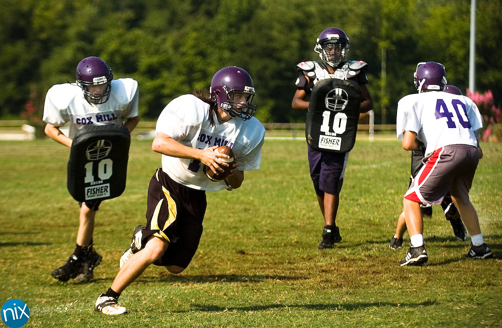Cox Mill's Arrick Hincer carries the ball while running through plays at the Charger's practice Friday morning.