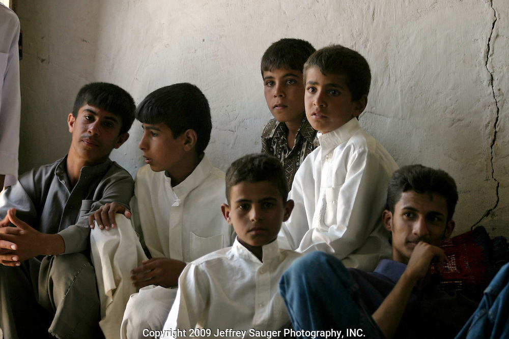 Young boys from the village gather at the Al-kasid family's Istikbal, or homecoming, in their home village Suq ash Shuyukh about 20 miles southeast of Nasiriyah, Iraq, Tuesday, July 29, 2003. The boys work throughout the 3 day celebration fetching water, serving food, cleaning, etc., which teaches them respect for their elders. In return, they are fed better than normal and get to be a part of the action as this was a huge event in the village...When Malik Al-kasid's caravan approached, guns were fired to announce his family's arrival. The welcming party then, returns fire to welcome him. The two parties move toward each other dancing and shooting until they join in the middle where the Hawaies occurs. ..The Al-kasid family fled Iraq after the Gulf War and their part in the uprising against Saddam Hussein in 1991, spent 3 years in Rafa, Saudi Arabia and finally settled in Dearborn, MI. The family hasn't been home to Iraq in 13 years.