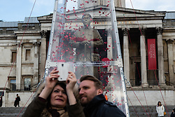 © Licensed to London News Pictures. 07/11/2014. London, UK. Two tourists take a selife in from the The Every Man Remembered First World War sculpture by artist, Mark Humphrey, that was unveiled by the Royal British Legion in Trafalgar Square, central London today. The brass sculpture, loosely based on the Unknown Solider, stands on a plinth of limestone sourced from the Somme and is encased in a Perspex obelisk, surrounded by poppies which float up around the figure every five minutes. Photo credit : Vickie Flores/LNP